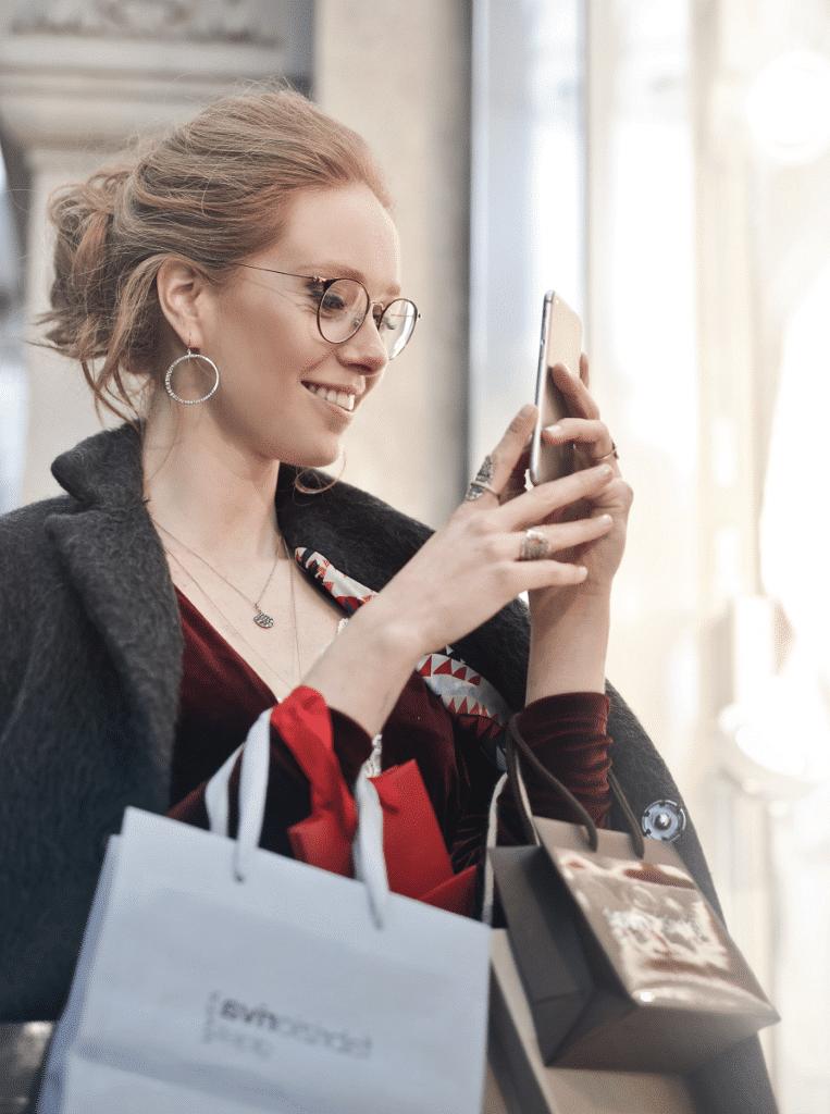 Femme dans la rue tenant un smartphone dans les mains